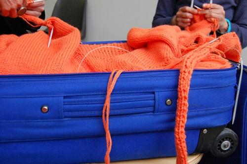 Aus dem leeren Inneren eines blauen Rollkoffers quillt die gestrickte cozy chaos art.